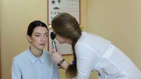 Lekarka egzamininuje pacjentów oczy z oftalmoskopem zdjęcie wideo