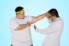 Lekarka egzamininuje rękę jego gruby pacjent z calipers zdjęcia stock