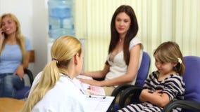 Lekarka i dziewczyna ono uśmiecha się podczas gdy siedzący w poczekalni zdjęcie wideo