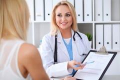 Lekarka i pacjent dyskutuje coś podczas gdy siedzący przy stołem przy szpitalem Medycyny i opieki zdrowotnej pojęcie zdjęcie stock