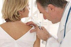 Lekarka i pacjent patrzeje dla skóry choroby - Fotografia Stock