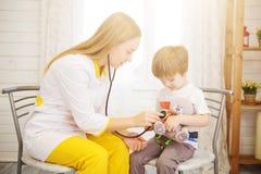 Lekarka i pacjent w domu Mała dziewczynka ono egzamininuje pediatra z stetoskopem opieki zdrowie medycyna zdjęcie stock