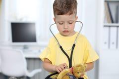 Lekarka i pacjent w szpitalu Szczęśliwa chłopiec ma zabawę podczas gdy egzamininujący z stetoskopem opieka zdrowotna i Fotografia Royalty Free