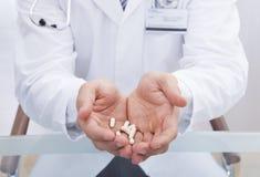 Lekarka lub męska pielęgniarka w lab żakieta mienia białych pastylkach Fotografia Royalty Free