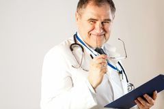 Lekarka medycyna uśmiechy, trzymający szkła i falcówkę dla rejestrów obraz stock