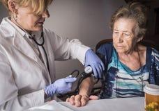 Lekarka mierzy arterialnego napięcie oldster w domu zdjęcie royalty free