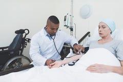 Lekarka mierzy naciska na kobiecie Kobieta przechodzi rehabilitację po leczenia raka zdjęcie royalty free