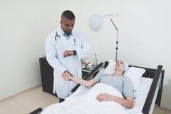 Lekarka mierzy puls kobieta Kobieta przechodzi rehabilitację po leczenia raka fotografia stock