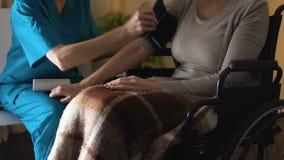 Lekarka na wywoławczym pomiarowym ciśnieniu krwi, posłuszny cierpliwy obsiadanie w wózku inwalidzkim zbiory