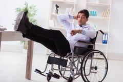 Lekarka odpoczywa na wózku inwalidzkim w szpitalu po nocnej zmiany Zdjęcie Stock
