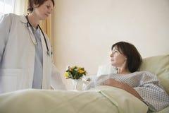 Lekarka pacjentem W łóżku szpitalnym zdjęcie stock