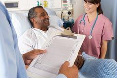 Lekarka Patrzeje mapę Z Starszym Męskim pacjentem Obrazy Royalty Free