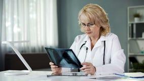 Lekarka patrzeje obraz cyfrowego, egzamininuje promieniowanie rentgenowskie cierpliwi płuca, opieka zdrowotna, medycyna fotografia stock