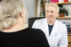 Lekarka Patrzeje Starszego pacjenta W biurze obraz royalty free