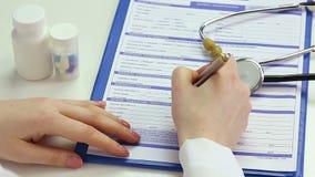 Lekarka pisze puszka pacjenta informaci, wypełnia wewnątrz rejestracyjną formę przy kliniką zbiory wideo