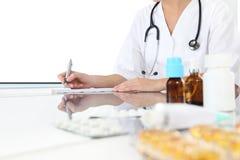 Lekarka pisze recepcie w medycznym biurze z lekami obrazy stock