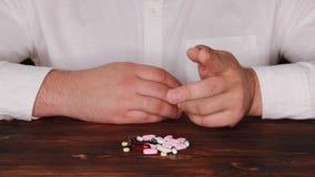 Lekarka podnosi pigułkę od stosu rozrzuceni ones Nałogowiec wybiera pigułkę Pastylki rozpraszają na stole zbiory