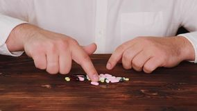 Lekarka podnosi pigułkę od stosu rozrzuceni ones Nałogowiec wybiera pigułkę Pastylki rozpraszają na stole zbiory wideo