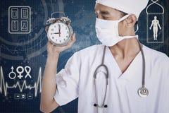Lekarka pokazuje budzika Obrazy Stock