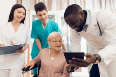 Lekarka pokazuje coś na pastylce starszy pacjent w karmiącym domu obraz royalty free