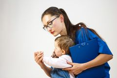 Lekarka robi małemu dziecko egzaminowi, on patrzeje jego ręki dzieci bawią się z stetoskopem obrazy stock