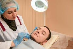 Lekarka robi ołówkowym konturom na pacjencie zdjęcia stock