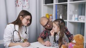 Lekarka rozkazy Kobiety lekarka w biurze w med klinice pisze za przydziale dla dziecko pacjenta ojciec zbiory wideo