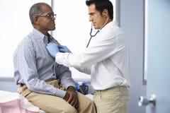 Lekarka Słucha Męska pacjent klatka piersiowa W operaci Zdjęcie Stock