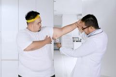 Lekarka sprawdza grubą rękę jego pacjent z calipers zdjęcia stock
