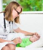 Lekarka sprawdza temperaturę dotyka jego czoło dziecko obraz stock