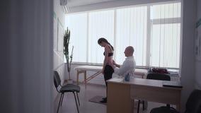 Lekarka sprawdza tylnego warunek młodych kobiet ludzie w gym sprawności fizycznej terapii kobiecie przy lekarki biura lekarką zdjęcie wideo