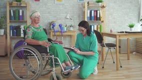Lekarka sprawdza zdrowie starsza kobieta w wózku inwalidzkim zdjęcie wideo