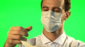 Lekarka stawia dalej maskowe i chirurgicznie rękawiczki - zielony ekran zbiory