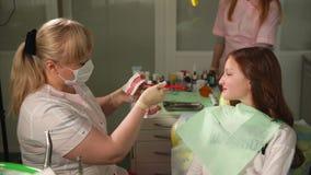 Lekarka stomatologiczna klinika pokazuje nastolatkowi dlaczego stosownie szczotkować jego zęby zbiory