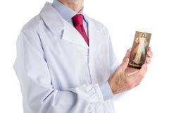 Lekarka trzyma Litościwą Jezusową ikonę w białym żakiecie Zdjęcie Stock