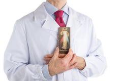 Lekarka trzyma Litościwą Jezusową ikonę w białym żakiecie Obraz Royalty Free