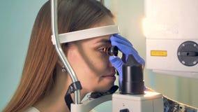 Lekarka trzyma oddzielnego obiektyw blisko do kobiety oka zbiory