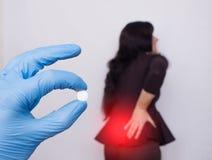 Lekarka trzyma pigułkę dla ból pleców, w tle dziewczyna medicament która tylnego osteochondrosis i rupturę, zdjęcia stock