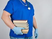 lekarka w błękitów jednolitych i bezpłodnych lateksowych rękawiczka chwytach w jego ręce sterta książki na szarym tle obrazy stock