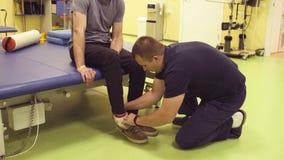 Lekarka w centrum rehabilitacji stawia dalej buty dla niepełnosprawnego mężczyzna zbiory