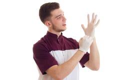 Lekarka w dodatków specjalnych ubraniach stawia dalej białe rękawiczek ręki na białym tle Fotografia Royalty Free