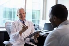 Lekarka W konsultacji z Męskim pacjentem W biurze Obraz Stock