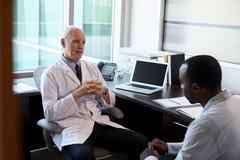 Lekarka W konsultacji z Męskim pacjentem W biurze Fotografia Stock