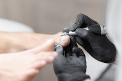 Lekarka w rękawiczkach robi procedurze dla stopy z specjalnym wyposażeniem Obrazy Stock