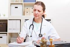 Lekarka z kartotekami w jej biurze Obraz Royalty Free