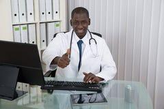 Lekarka Z kciukiem Up W Frontowym komputerze Przy biurkiem Fotografia Stock