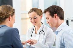 Lekarka z pacjentami w konsultować w klinice Obraz Stock