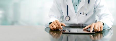 Lekarka z pastylka komputerem przy szpitalnym biurem fotografia stock