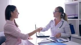 Lekarka z pozytywnym dobre'em wieści utrzymuje promieniowanie rentgenowskie w jego ręce i mówi o zdrowie młoda kobieta w klinice  zdjęcie wideo