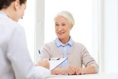Lekarka z schowka i seniora kobietą przy szpitalem Obrazy Stock